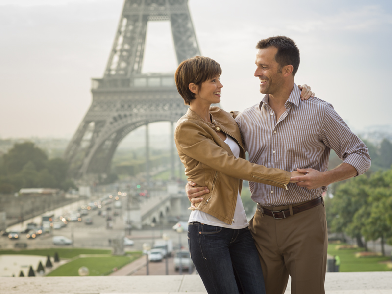 A couple posed by the Eiffel Tower in Paris, France