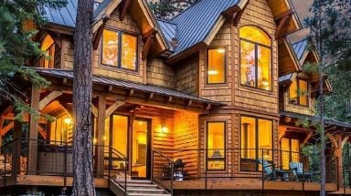 The front of a luxury cabin home in Oregon with lots of windows to take in the scenic mountain views
