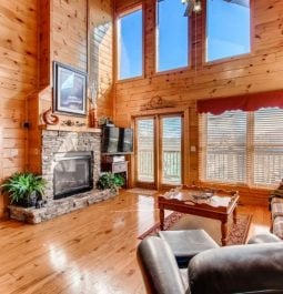 A spacious living room with wooden accents, large windows and stone fireplace