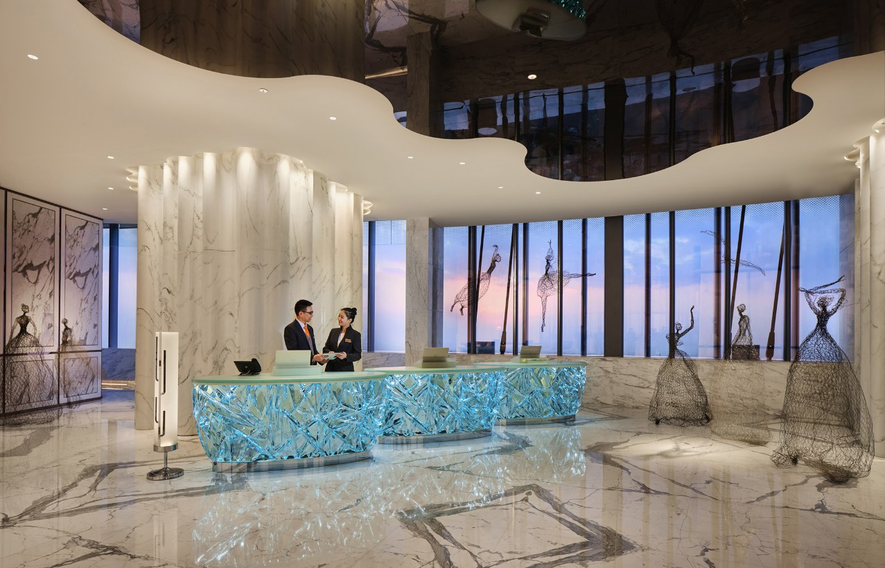 The reception desk at J Hotel Shanghai Tower is surrounded by marble and chandeliers.
