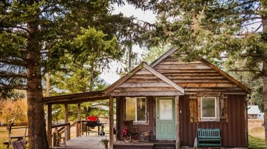 side view of wood cabin with front porch and outdoor area