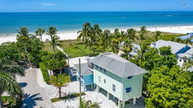 green house sitting on beach with blue water