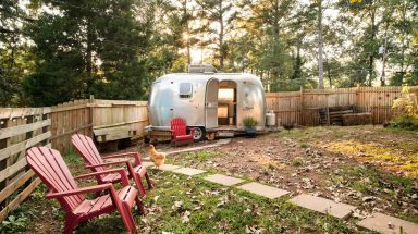 Camper in a fenced yard with chicken and seating