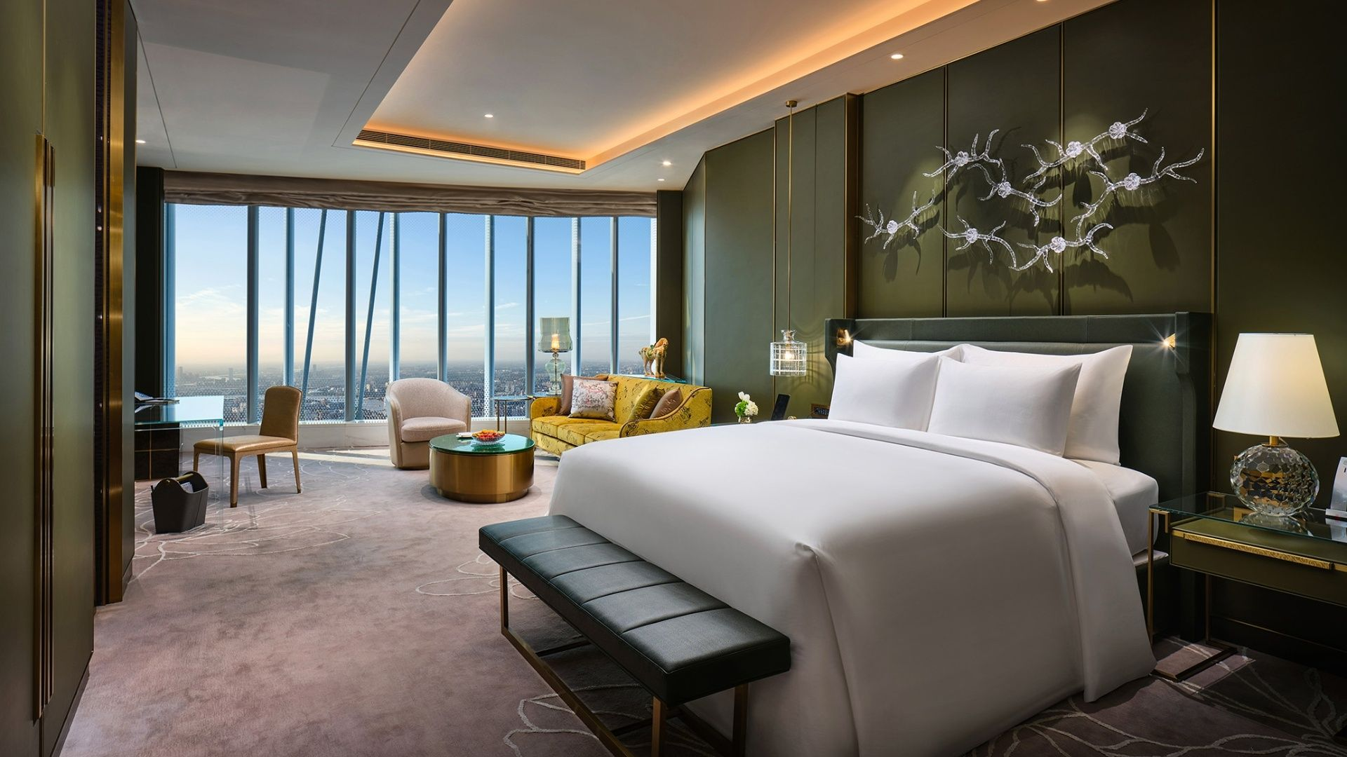 The New Chinese Style stateroom at J Hotel Shanghai Tower features rich leather furniture and dragon patterned sofas.