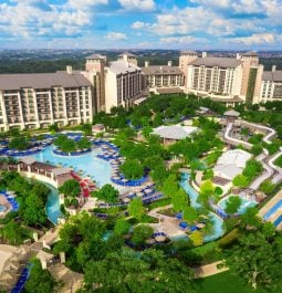 aerial view of resort with swimming pools and greenery