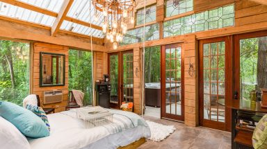 A chandelier and swing bed hang in the middle of a bedroom with floor-to-ceiling windows illuminating this Texas cabin
