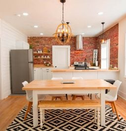 dining area and kitchen with brick wall and accent lights