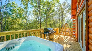 cabin deck with hot tub, swing, and grill