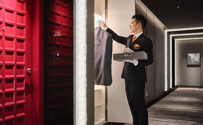 A personal butler hangs laundry in a closet at the J Hotel Shanghai Tower
