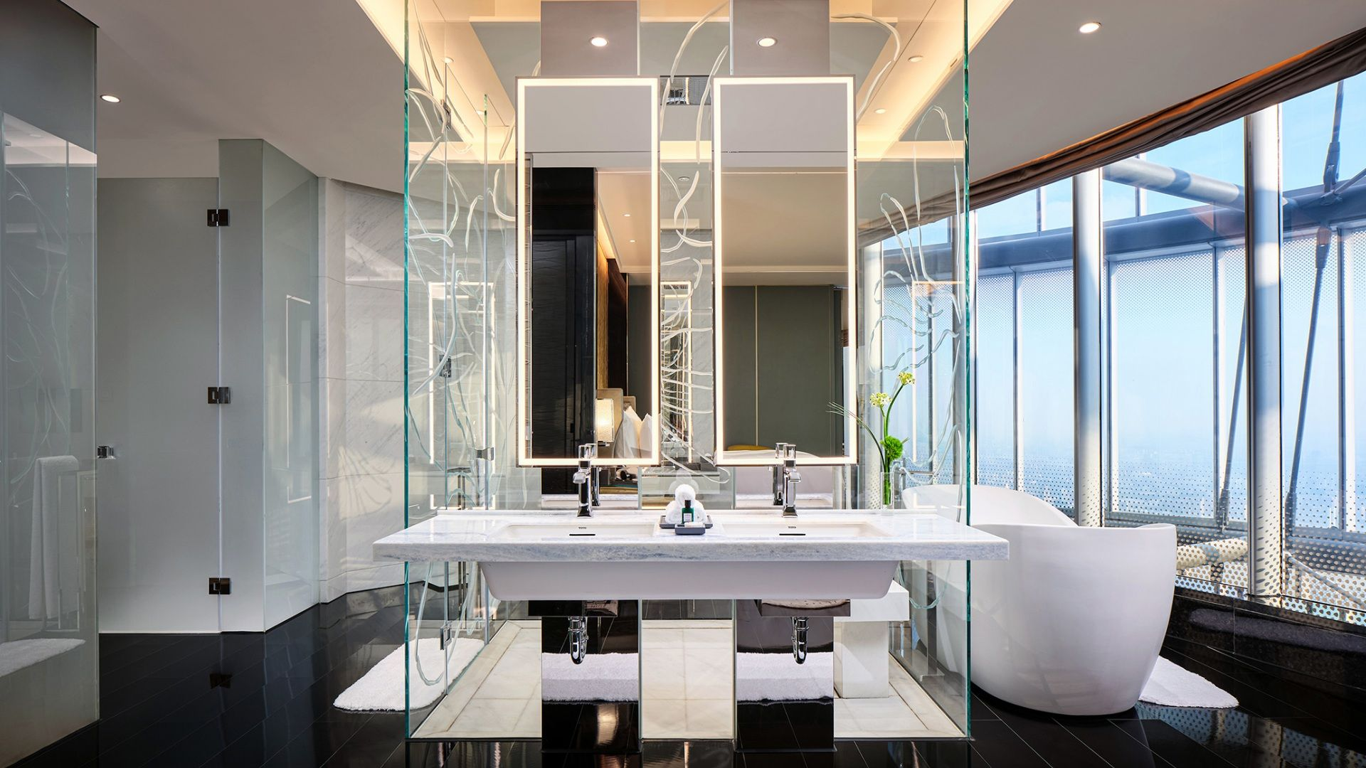 The modern glass shower and magnolia pedal bathtub have skyline views in the J Suite at the J Hotel Shanghai Tower.
