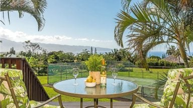 Glass table overlooking palm tree and ocean views at Pupukea Home