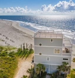 Aerial view of a stand-alone beach house with ocean views from every angle