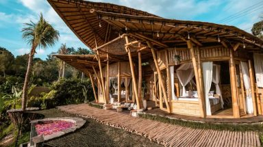 The exterior of an open-air bamboo house in Bali with an outdoor hot tub