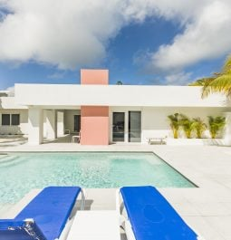 sun loungers set by a sparkling pool and white and pink building
