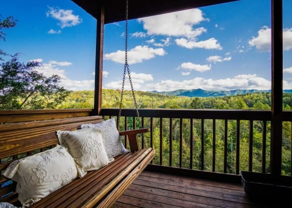A swing on one of three decks overlooking a lush forest from the Cliffhang Over the French Broad River home.