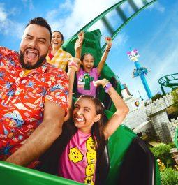 Family smiling while riding roller coaster at LEGOLAND Florida