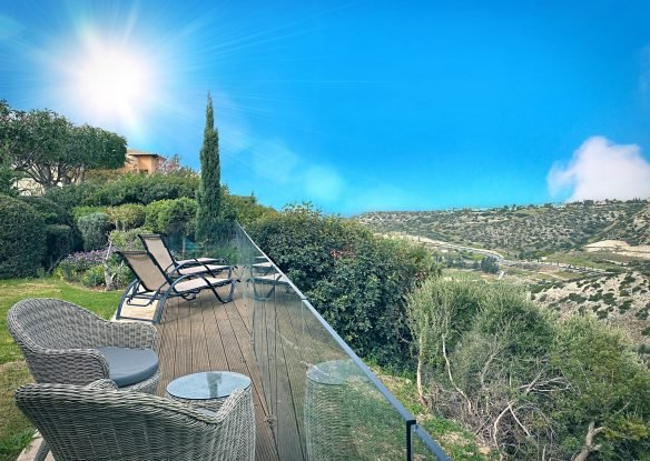A terrace with lounge chairs overlooking the the stunning scenery of Aphrodite Hills in Cypress
