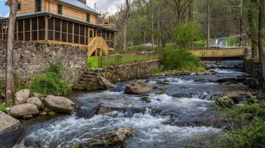 Roaring river going past wooden cabin