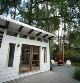 Exterior of a modern tiny home in Gainesville surrounded by lush landscaping and tall trees