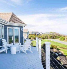 The spacious deck of a blue beach house overlooks the ocean