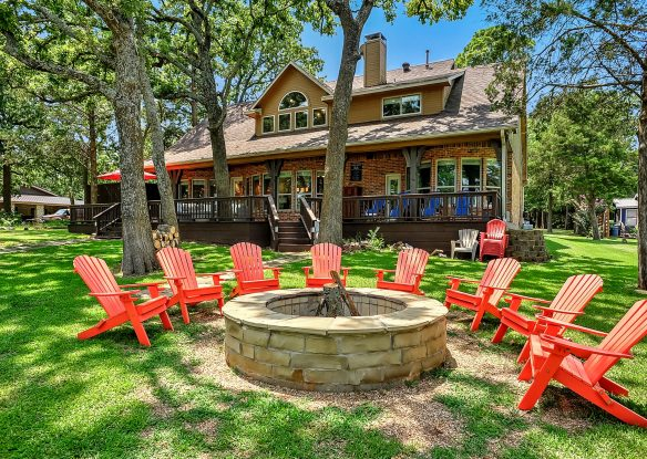 fire pit surrounded by adirondack chairs