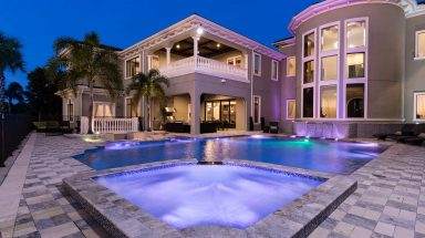 Evening exterior shot of house with swimming pool and white stone buildings