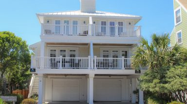 A tall beach house stands with multiple decks and a double garage