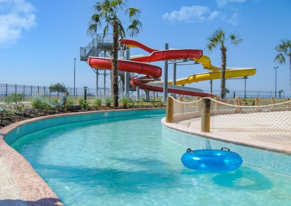 A tall water slide towers over a blue winding lazy river with inner tubes.