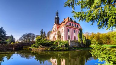 Pink toned castle on glassy lake with bright blue skies